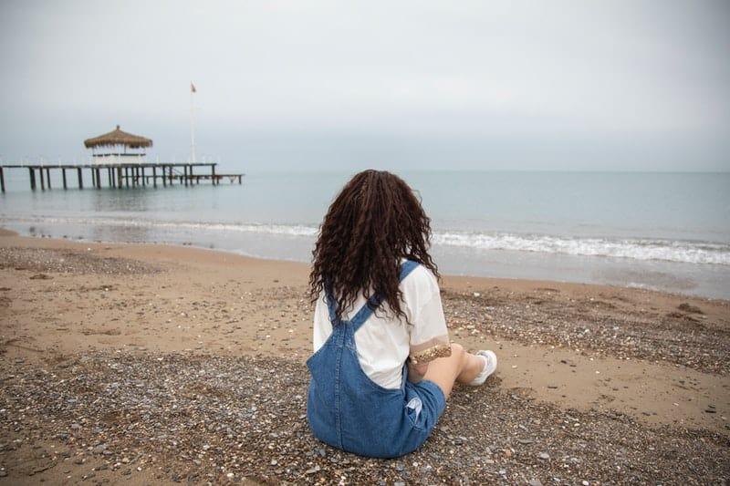 Die Frau sitzt am Strand