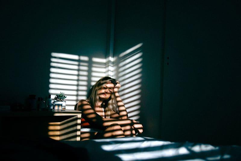 Die Frau sitzt in einem dunklen Raum