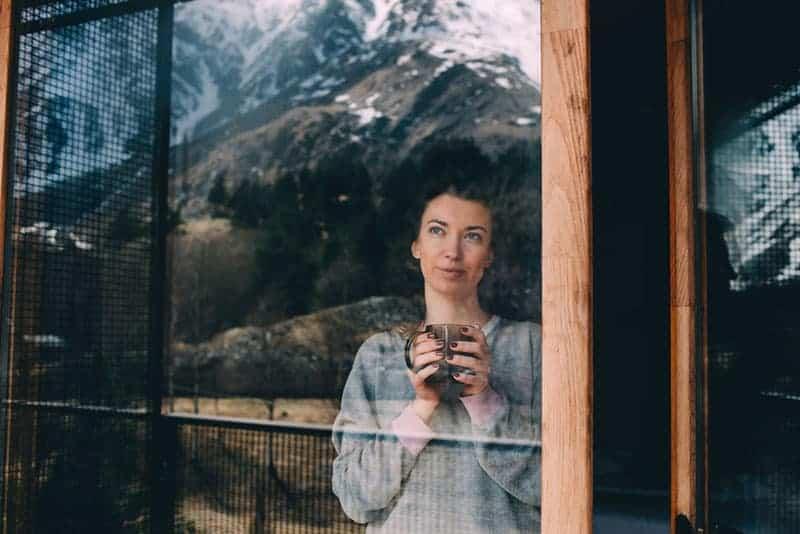 Die Frau trinkt und schaut aus dem Fenster