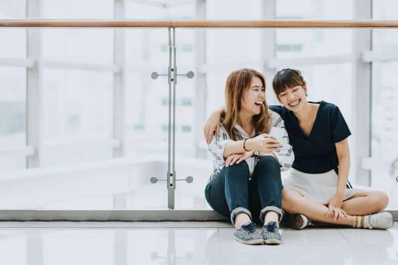 Die besten Freundinnen lachen und lächeln im Sitzen