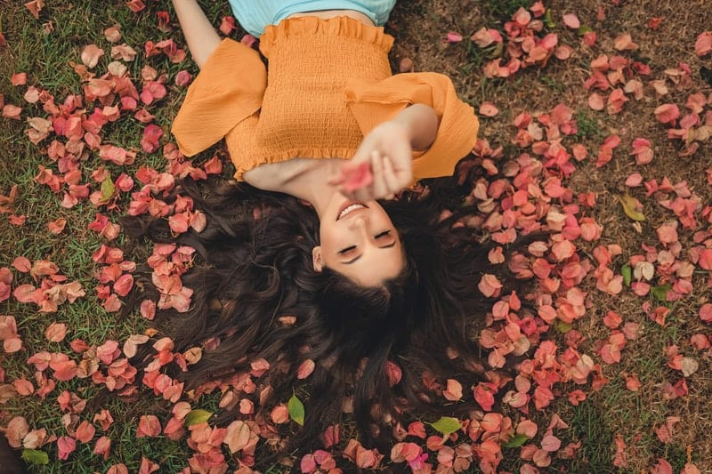 Die glückliche Frau liegt auf den Blumen