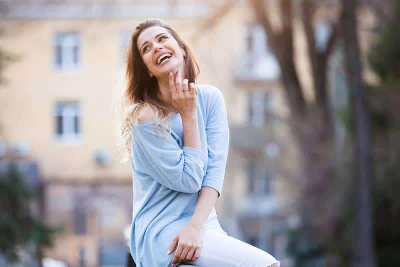 Draußen Porträt des schönen jungen Mädchens lachend