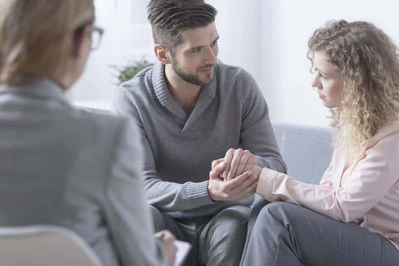 Ehemann entschuldigt sich bei seiner Frau während der Paartherapie