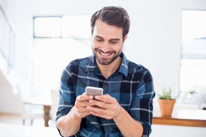 Ein Mann, der eine Nachricht über ein Handy sendet