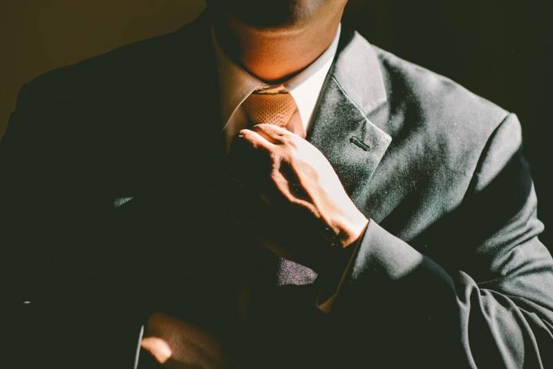 Ein Mann in einem schwarzen Anzug lockert seine Krawatte
