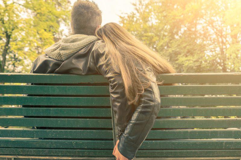 Ein Mann in einer Frau sitzt auf einer Bank