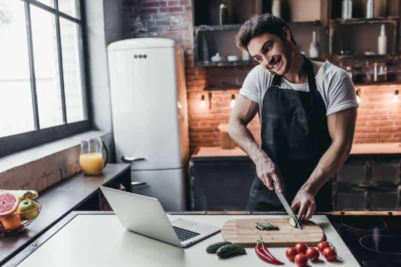 Ein Mann kocht und schaut auf einen Laptop