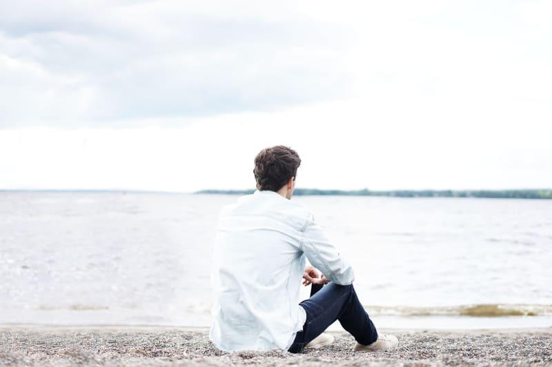 Ein Mann sitzt am Strand am Wasser