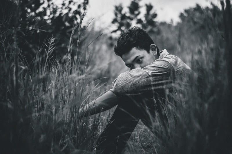 Ein Mann sitzt im Gras