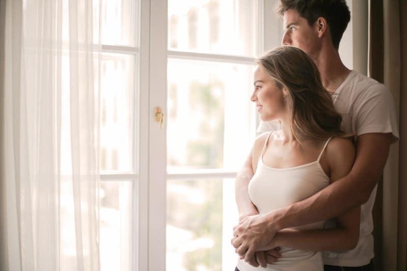 Ein Mann umarmt eine Frau am Fenster