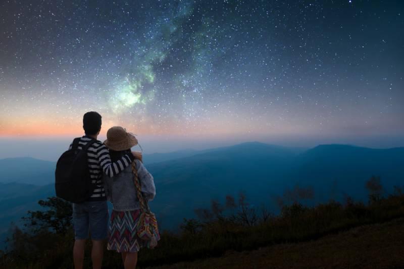 Ein Paar schaut in einer romantischen Nacht auf die Sterne am Himmel und die Milchstraße