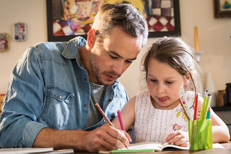 Ein Vater hilft seiner Tochter bei den Hausaufgaben