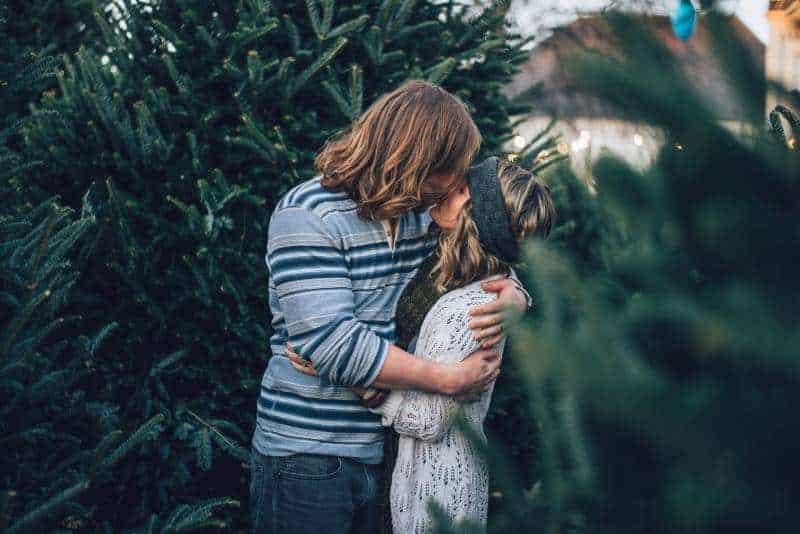 Ein langhaariger junger Mann küsst ein Mädchen