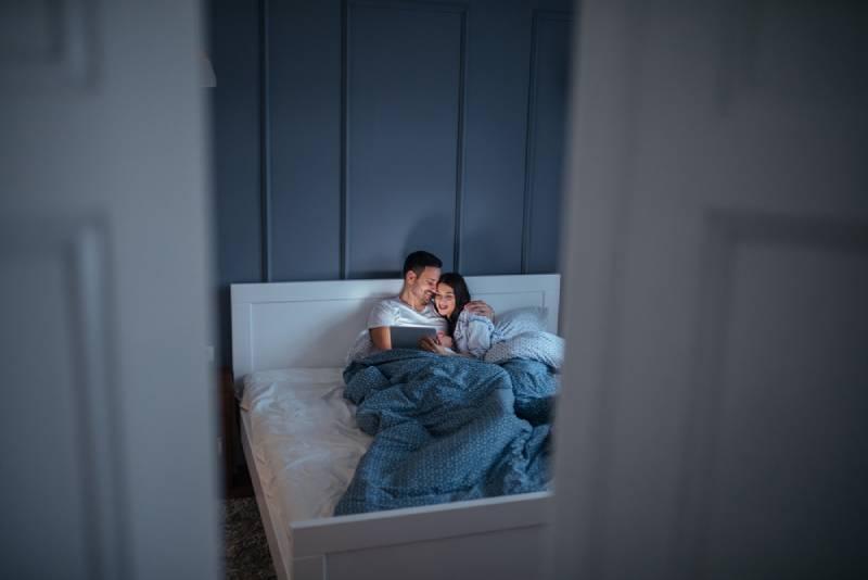 Ein schönes junges Paar kuschelt in ihrem warmen Bett