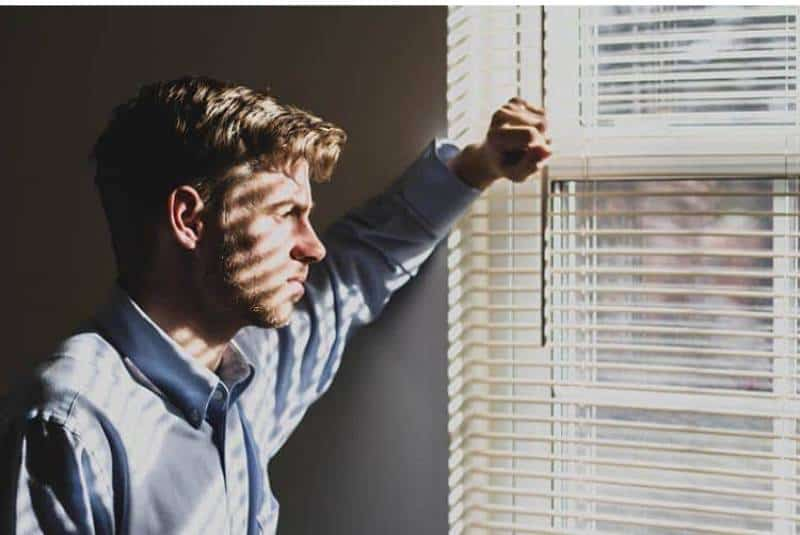 Ein stirnrunzelnder Mann schaut aus dem Fenster
