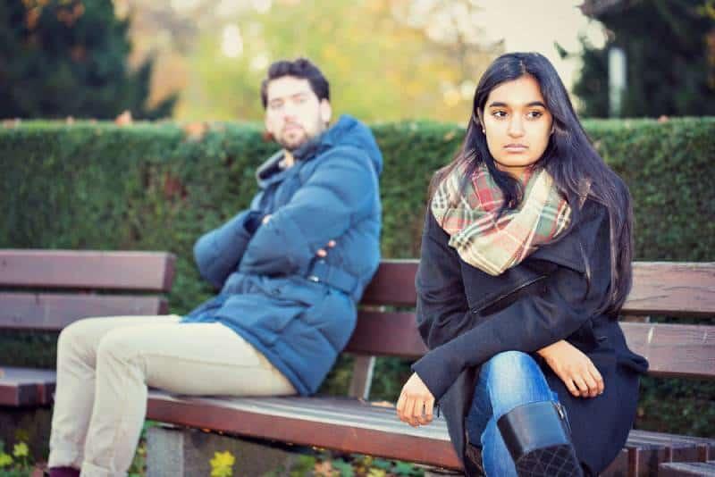 Ein verärgertes Paar, das auf einer Parkbank sitzt