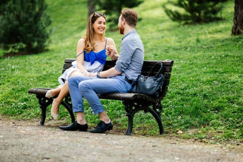 Ein verliebtes romantisches Paar, das auf einer Parkbank sitzt