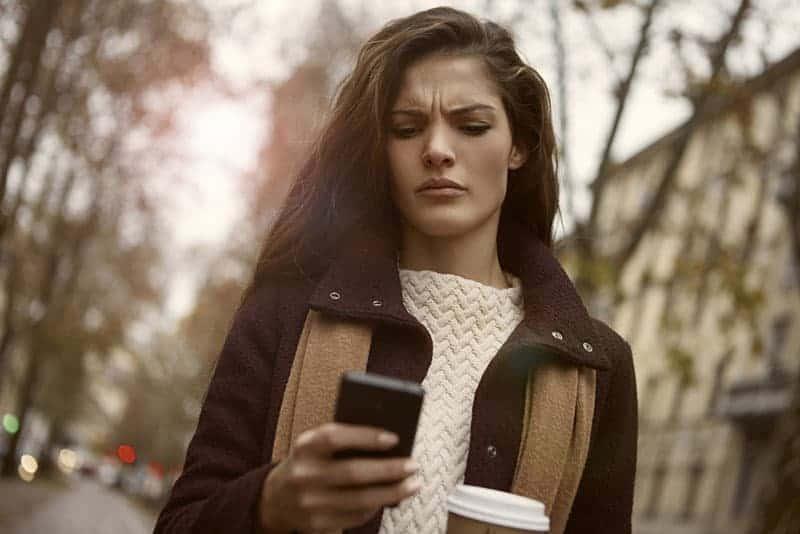 Ein wütendes Mädchen schaut auf das Telefon