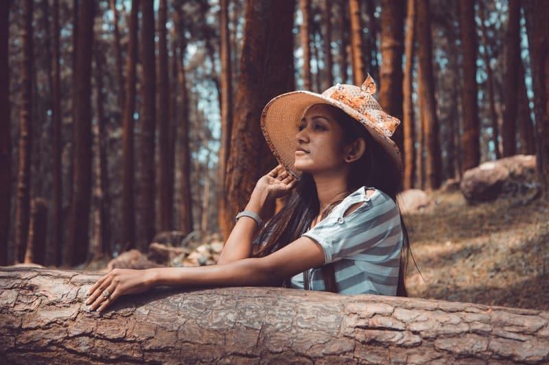 Eine Frau in einem Wald trägt einen Hut