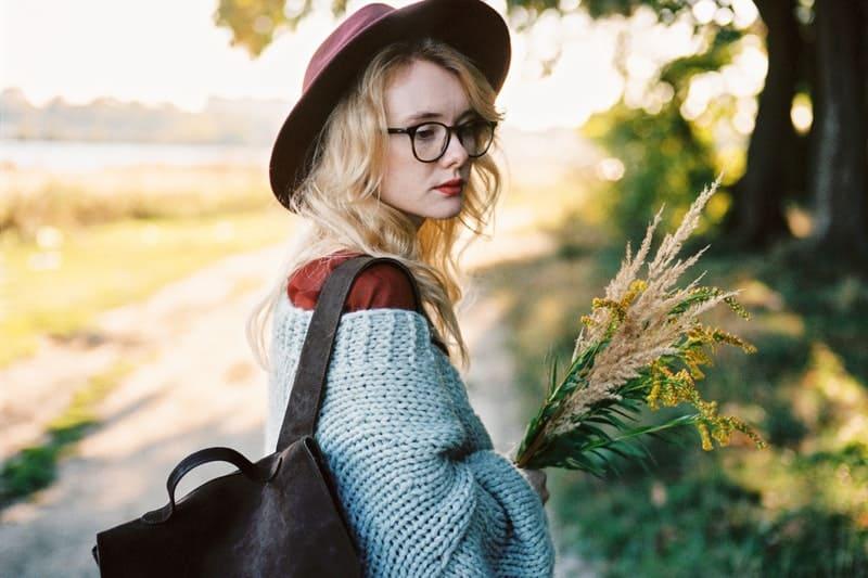 Eine Frau mit Hut hält Blumen