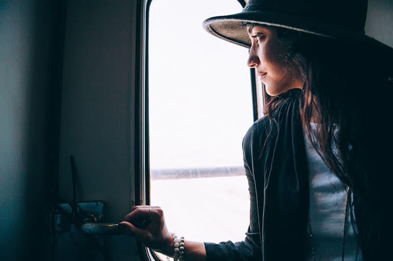 Eine Frau mit Hut schaut aus dem Fenster