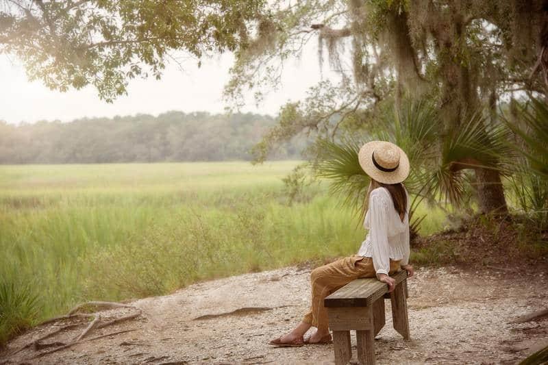 Eine Frau mit Hut sitzt auf einer Bank