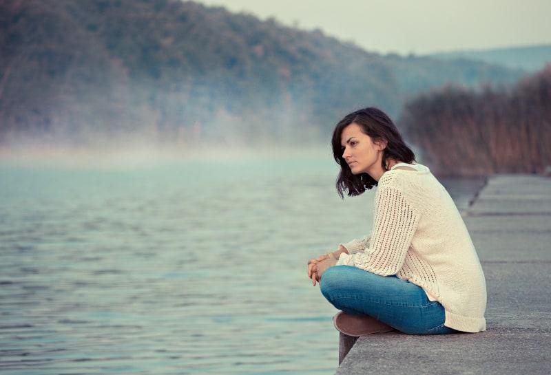 Eine Frau sitzt am See