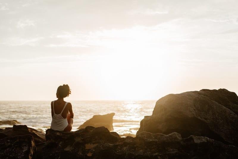 Eine Frau sitzt auf einem Stein