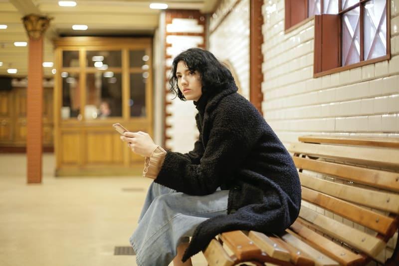 Eine Frau sitzt auf einer Holzbank