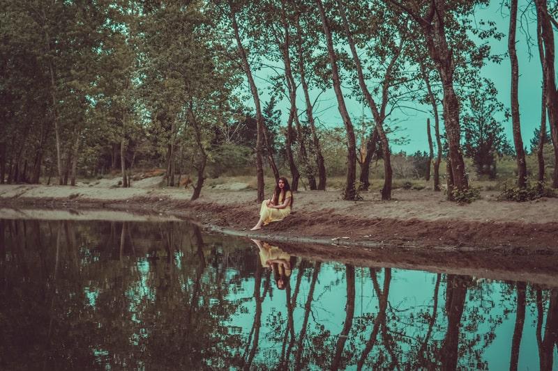 Eine Frau sitzt vor einem See
