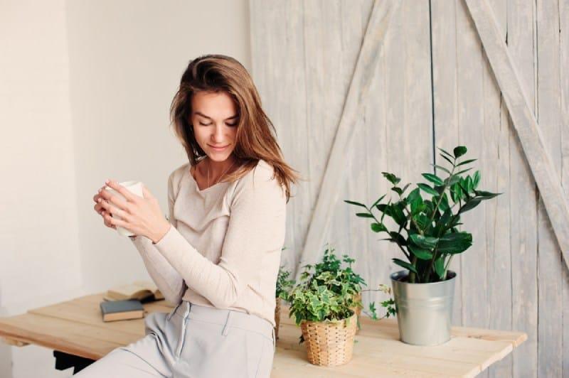 Eine Frau trinkt Kaffee und setzt sich auf einen Tisch