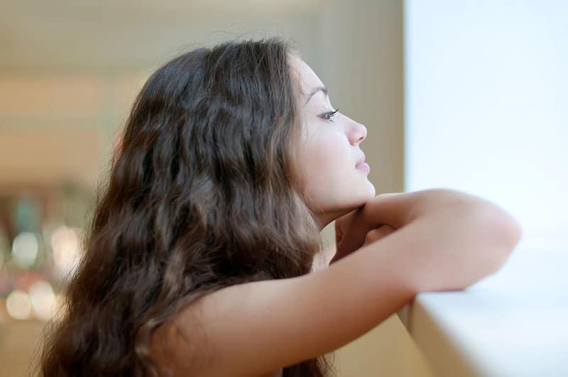 Eine nachdenkliche Frau schaut aus dem Fenster