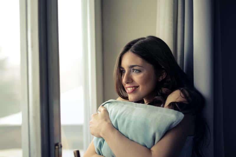Eine schöne Frau umarmte ein Kissen am Fenster