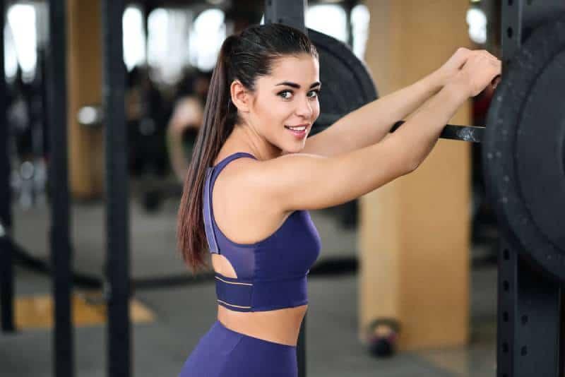 Eine schöne athletische junge brünette Frau in der Sportbekleidung im Fitnessstudio