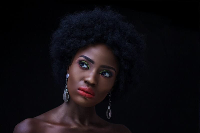 Eine schwarze Frau trägt Ohrringe