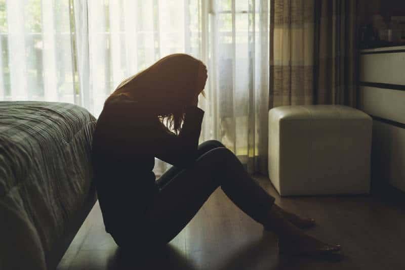 Einsame junge Frau depressiv und gestresst sitzend Kopf in Händen im dunklen Schlafzimmer,