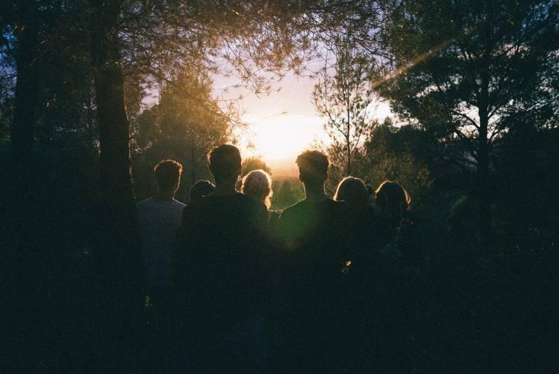 mehrere Leute beobachten den Sonnenaufgang mitten im Wald