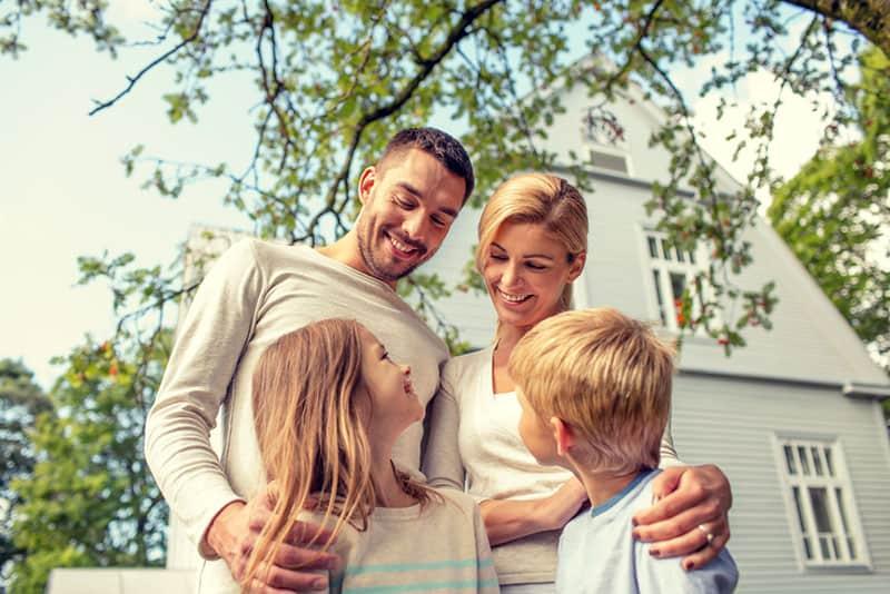 glückliche Familie, die vor Haus steht