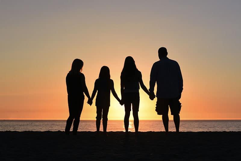 Familie, die ihre Hände im Sonnenuntergang zusammenhält
