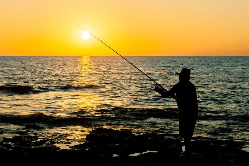 Fischer bei Sonnenuntergang angeln