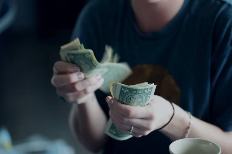 Fokusfotografie der Person, die Dollarbanknoten zählt