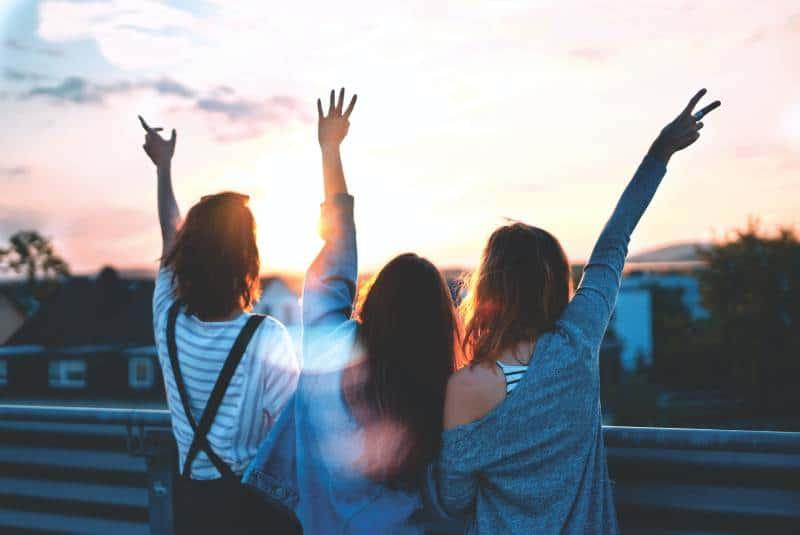 Foto von drei Frauen, die ihre Hände heben