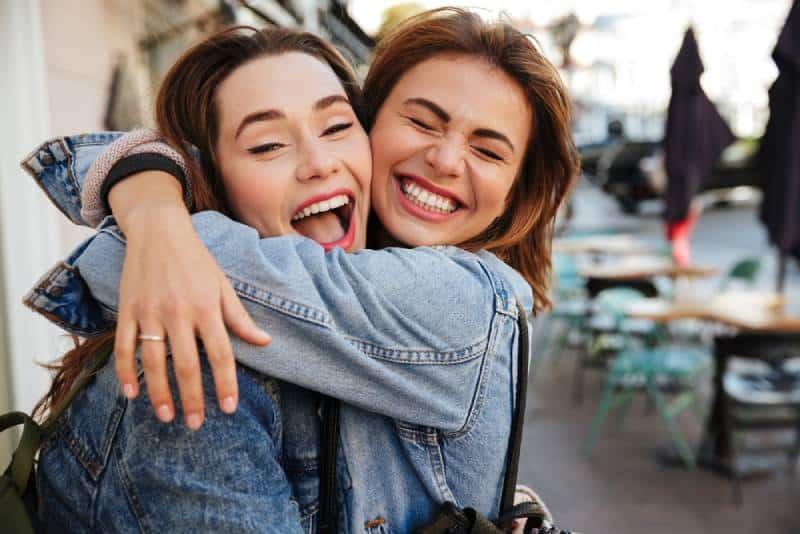 Foto von lachenden Freundinnen, die sich auf der Stadtstraße umarmen