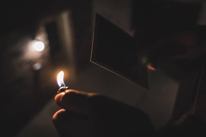 Fotografie mit flachem Fokus einer Person, die ein Feuerzeug hält