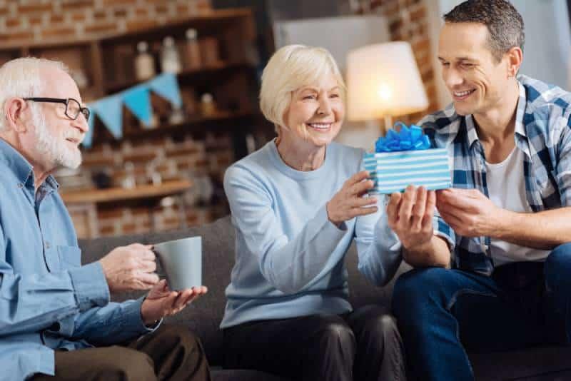 Fröhlicher junger Mann, der seiner glücklichen älteren Mutter ein Geburtstagsgeschenk gibt