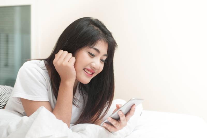 frau smile benutzt das smartphone und liegt zu Hause auf dem Bett