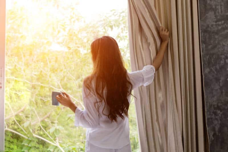 Frau am Morgen, die eine Tasse Tee oder Kaffee hält und den Sonnenaufgang betrachtet
