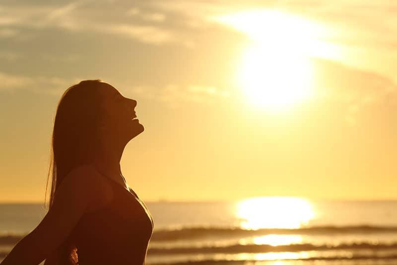 Frau atmet tief bei Sonnenuntergang
