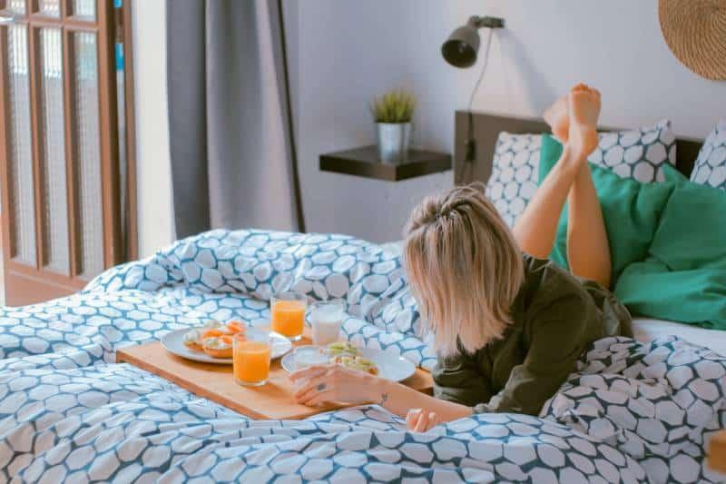 Frau auf dem Bett liegend und Brett haltend