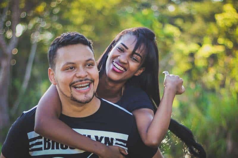 Frau auf dem Rücken ihres lächelnden Mannes
